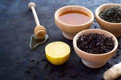 木碗用一块干茶和新鲜的蜂蜜、柠檬和姜 图库摄影