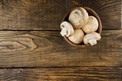 木碗用在木桌上的白色蘑菇 顶视图 免版税库存图片