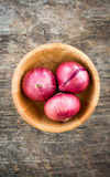 木碗用在老木背景的红洋葱 免版税库存图片