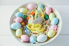 木碗用桔子、黄色,桃红色和绿色鸡蛋在白色木背景 复活节快乐!装饰 库存照片