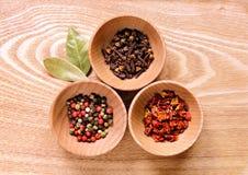 木碗用胡椒、丁香和辣椒粉 免版税库存照片