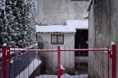 木窗口在一个多雪的屋顶和一个红色门佩萨罗,意大利下 免版税库存图片