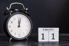 木立方体形状日历与黑时钟的2月11日 免版税库存图片