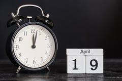 木立方体形状日历与黑时钟的4月19日 免版税图库摄影