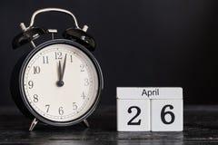 木立方体形状日历与黑时钟的4月26日 免版税库存照片