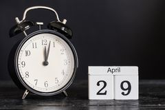 木立方体形状日历与黑时钟的4月29日 图库摄影
