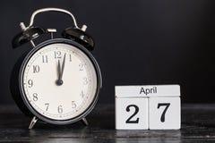 木立方体形状日历与黑时钟的4月27日 库存照片