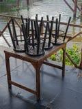 木筏的餐馆由运河在有黑木和金属椅子的乡下投入了棕色木桌 免版税库存照片