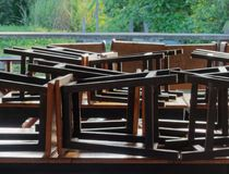 木筏的餐馆由运河在有黑木和金属椅子的乡下投入了棕色木桌 库存图片