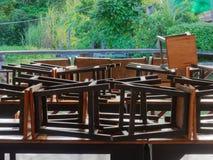 木筏的餐馆由运河在有黑木和金属椅子的乡下投入了棕色木桌 免版税库存图片