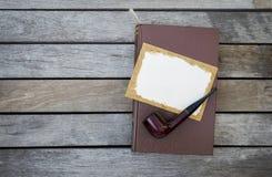 木管子和空白的老纸牌在棕色皮革盖子预定 免版税库存照片