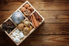 木箱用圣诞节装饰,球,门铃,坚果,锥体,桂香,在木背景的蛋白软糖填装了 节假日 免版税图库摄影
