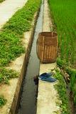 木篮子和蓝色鞋子在米领域和小运河附近 库存图片