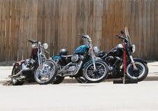 木篱芭停放的三辆摩托车 免版税库存照片