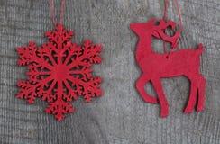 木红色圣诞节鹿和雪花在木背景 顶视图 免版税库存图片