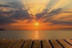 木纹理和美好的背景与海、太阳和云彩在五颜六色的日出 免版税图库摄影