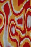 木纹理 修改过的表面饰板 波浪线,长圆形 抽象 背景红色,黄色和白色,与镇压 免版税库存照片