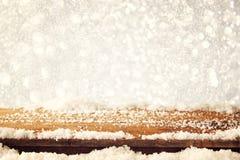 木老桌和12月新鲜的雪的图象在上面 在闪烁背景前面 选择聚焦 库存照片