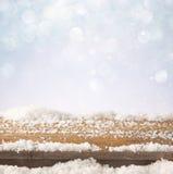 木老桌和12月新鲜的雪的图象在上面 在闪烁背景前面 选择聚焦 免版税库存照片