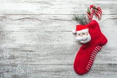 木背景、被绘的白色与圣诞节袜子和圣诞老人 在它和糖果上色的杉树 库存照片