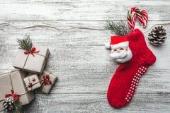 木背景、被绘的白色与圣诞节袜子和圣诞老人 在它和糖果上色的杉树 免版税库存照片
