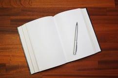 木背景书开放笔的表 免版税库存图片