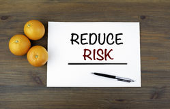 木背景用桔子和文本:减少风险 图库摄影