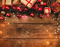 木背景,与红灯,玩具和礼物安排了在上面,正方形型,与电灯泡 库存照片