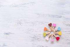 木背景绘与与五颜六色的心脏的白色油漆 心脏晒衣夹 结构树的纹理 免版税库存照片