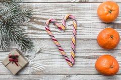 木背景 阿尔比 冷杉分支绿色 桔子 礼品 色的糖果的心脏 冬天卡片 空间圣诞节或新年 库存图片