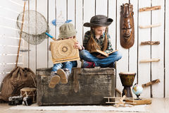木胸口观看的册页的两个逗人喜爱的小女孩 库存图片