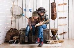 木胸口观看的册页的两个逗人喜爱的小女孩 库存照片