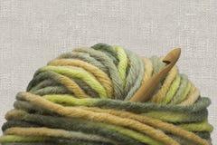 木自然竹钩针、绿色毛线羊毛球和钩针编织盘旋在亚麻制背景的照片 hom的创造性的工作地方 库存图片