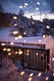 木花园大门在与bokeh圣诞灯的冷和多雪的冬天夜在前景 免版税库存图片