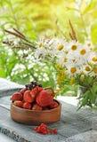 木花瓶用草莓和红浆果在雏菊花束的背景  库存照片