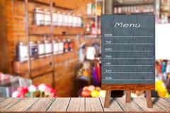木菜单显示标志,在木桌,被弄脏的图象背景上的一个框架餐馆留言簿 库存照片