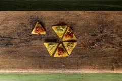 木表面上安排的烤干酪辣味玉米片芯片 免版税图库摄影