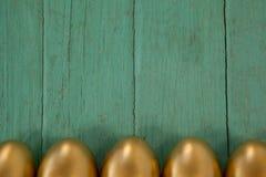 木表面上安排的金黄复活节彩蛋 免版税库存照片