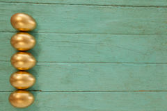 木表面上安排的金黄复活节彩蛋 免版税库存图片