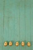 木表面上安排的金黄复活节彩蛋 库存图片