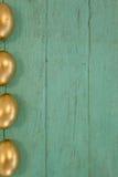 木表面上安排的金黄复活节彩蛋 库存照片