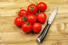 木表面上有红色小蕃茄和刀子 免版税库存照片