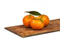 木表面上的三个成熟橙色蜜桔 免版税图库摄影