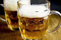 木表面上的啤酒杯 库存图片