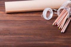 木表面上的学校用品 在玻璃和纸卷的色的铅笔在一张木桌上的 库存照片