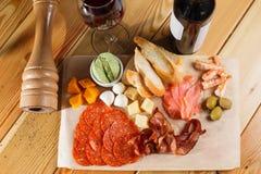 木表面上的开胃小菜盛肉盘 玻璃瓶酒 不同的快餐 免版税库存照片