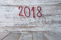 木表面上的新年2018年背景与发光的数字 库存图片