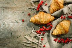 木表面上的新月形面包在一个羊毛一揽子和红色莓果中 秋天动机 免版税图库摄影