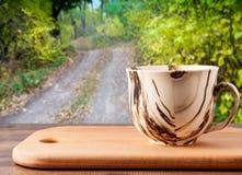 木表面上的杯在一条森林公路的背景有树的 免版税库存照片