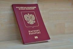 木表面上的红色俄国在西里尔字母的护照与说明护照和俄罗斯联邦 免版税库存图片
